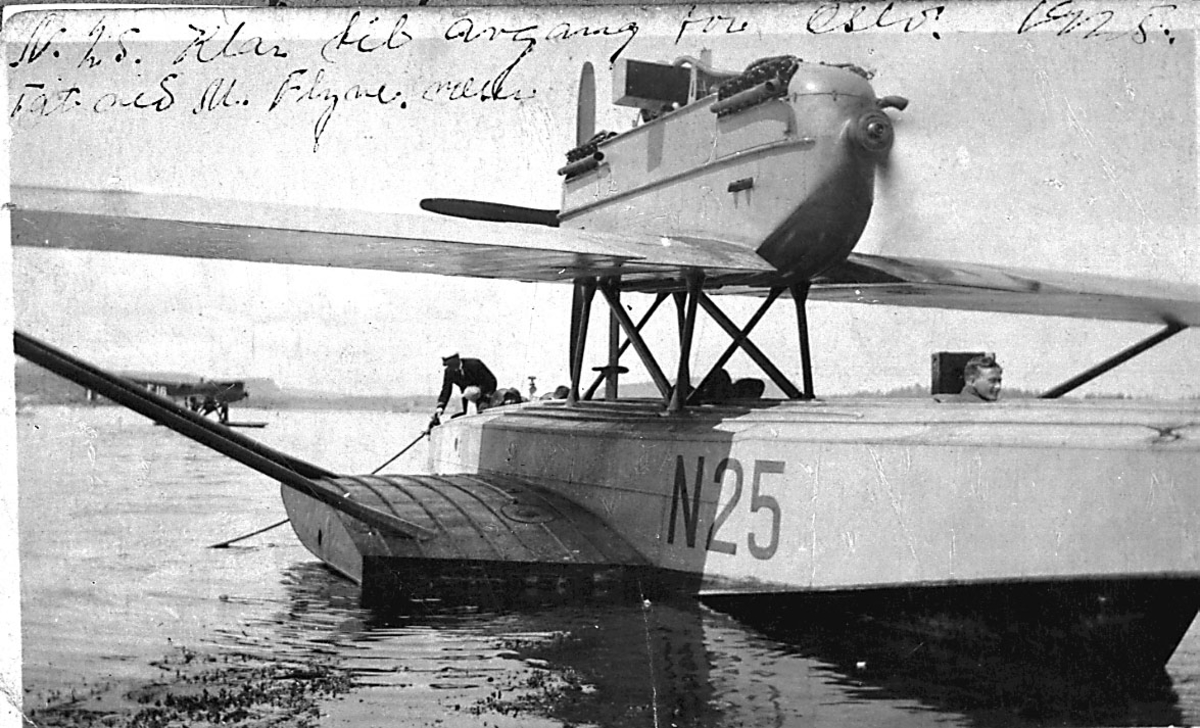 1 fly ligger stille på havoverflata, 2 personer ombord. Dornier-Wal N25.  1 annet sjøfly i bakgrunnen.