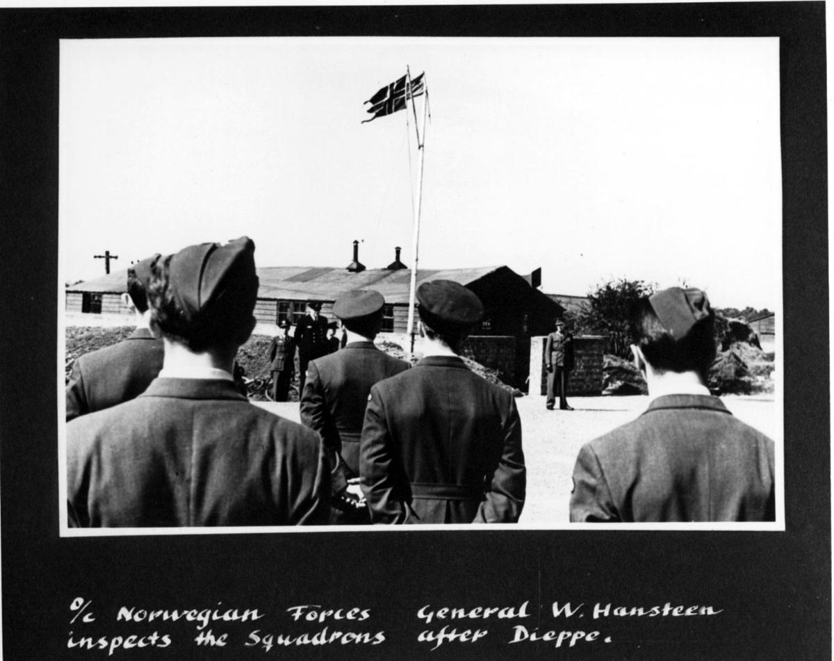 Flere personer i militæruniform, offiserer, soldater. Personene foran med ryggen i mot. Bak sees stang - mast med 2 flagg, og bygning. Håndskrevet engelsk tekst under bildet.