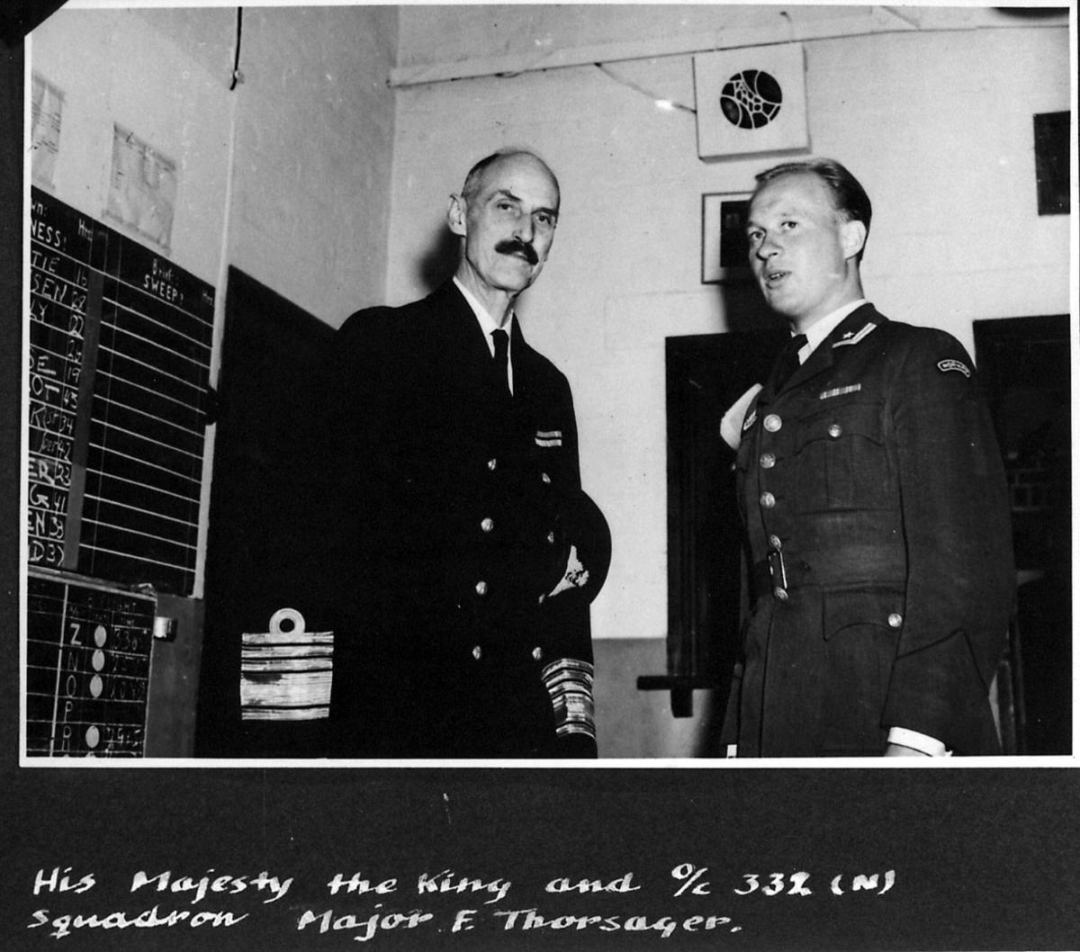 2 personer i militæruniform. Kong Haakon VII og Major F.Thorsager. Bildet tatt innendørs. Håndskrevet engelsk tekst under bildet.