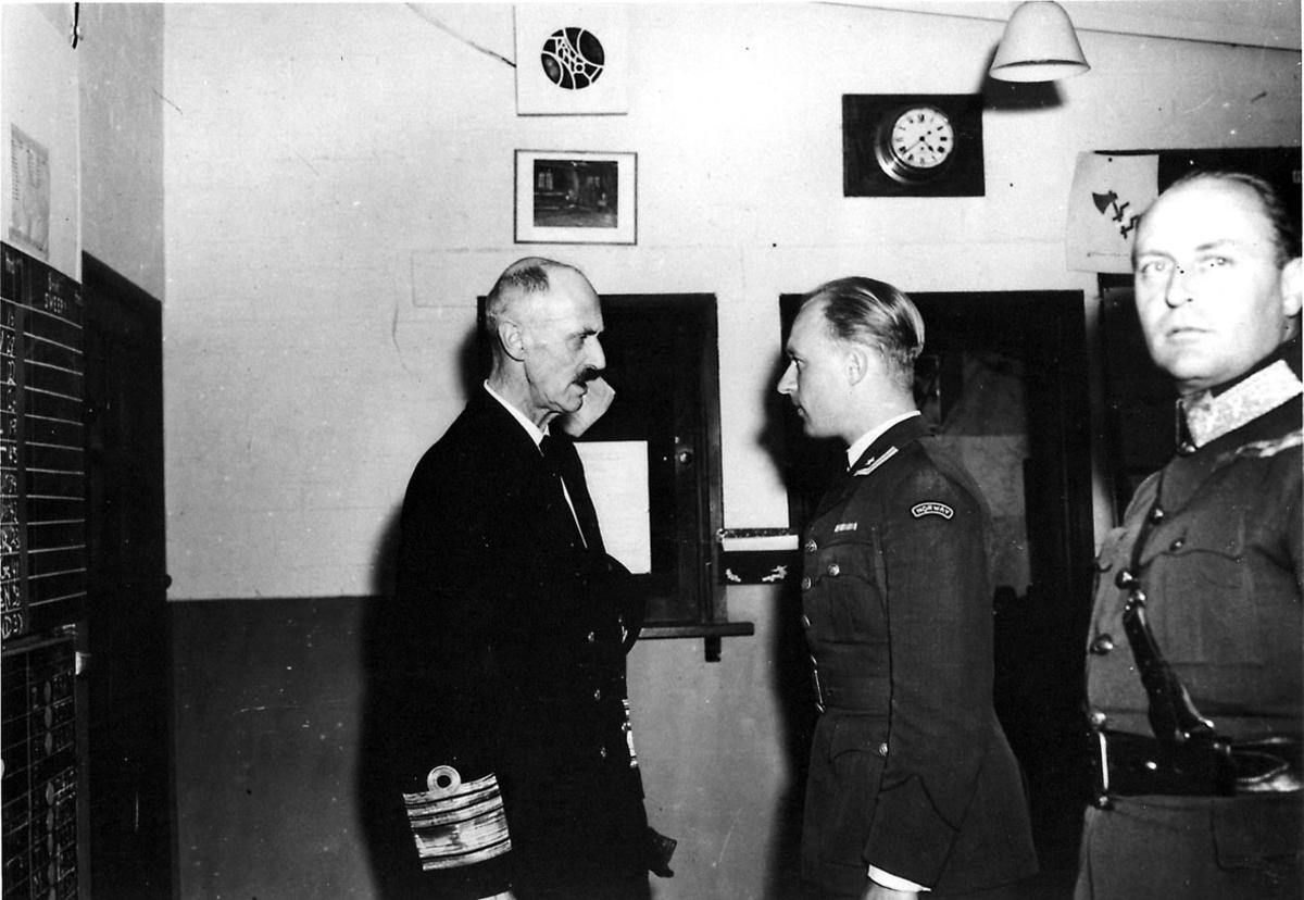3 personer i militæruniform. Kong Haakon og Kronprins Olav, sammen med en offiser. Bildet tatt innendørs.