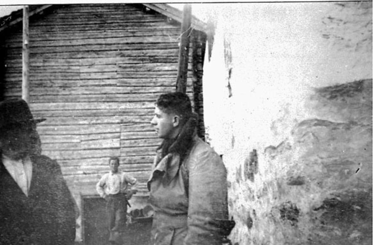 Tre personer foran. Bak sees røstveggen på tømmerbygning.