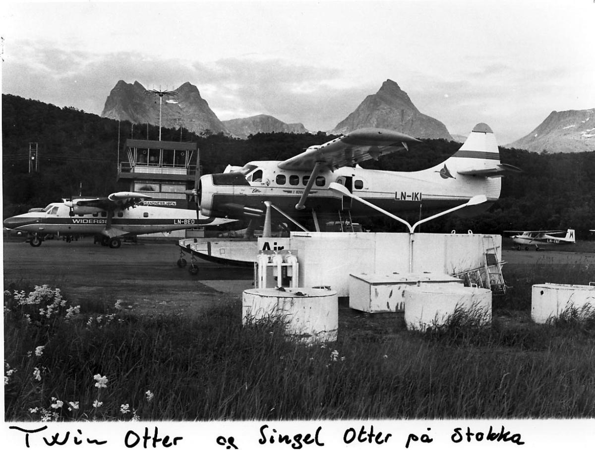Lufthavn, 3 fly, bak t.v. DHC-6 Twin Otter, LN-BEO, fra widerøe, sett fra siden. Foran DHC-3 Otter, LN-IKI, fra Norving, sett fra siden. Mindre fly t.h. Bak sees kontrolltårnet. Fjell i bakgrunnen.