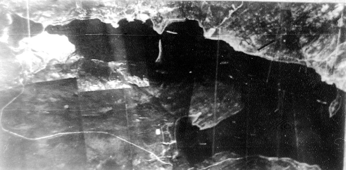 Luftfoto. Landskap med fjord, noen bygninger og veier. Noe russisk tekst på bildet.