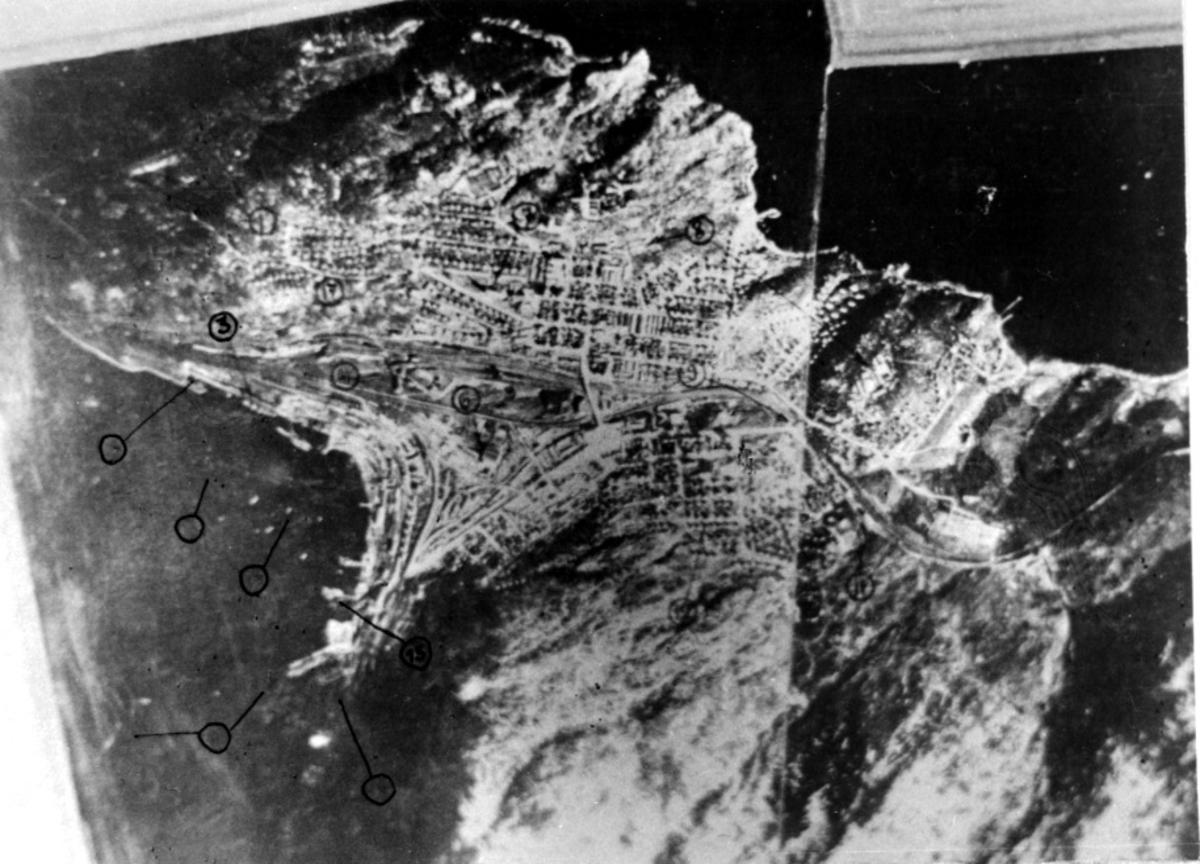 Luftfoto. Nedenfor sees tettsted. Flere områder er avmerket for hånd på bildet.