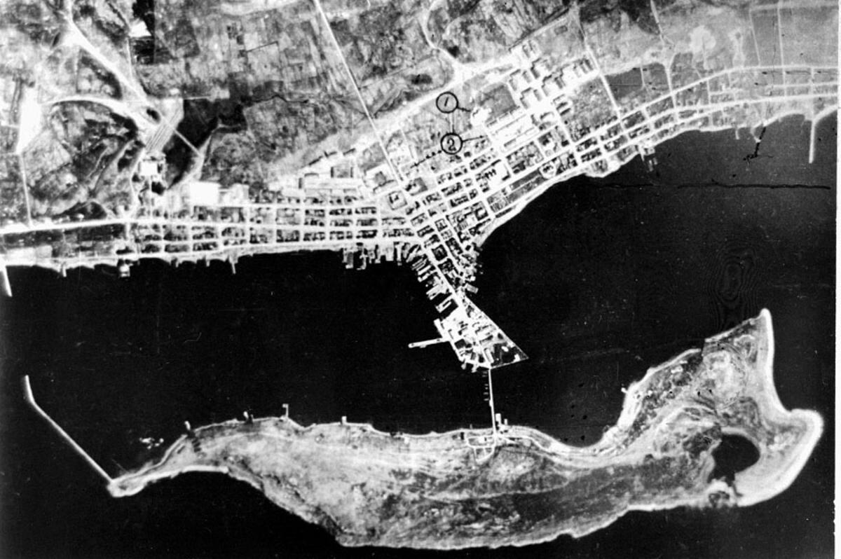 Luftfoto av tettsted ute ved kysten. Bebyggelse, havneanlegg, gater og veier.