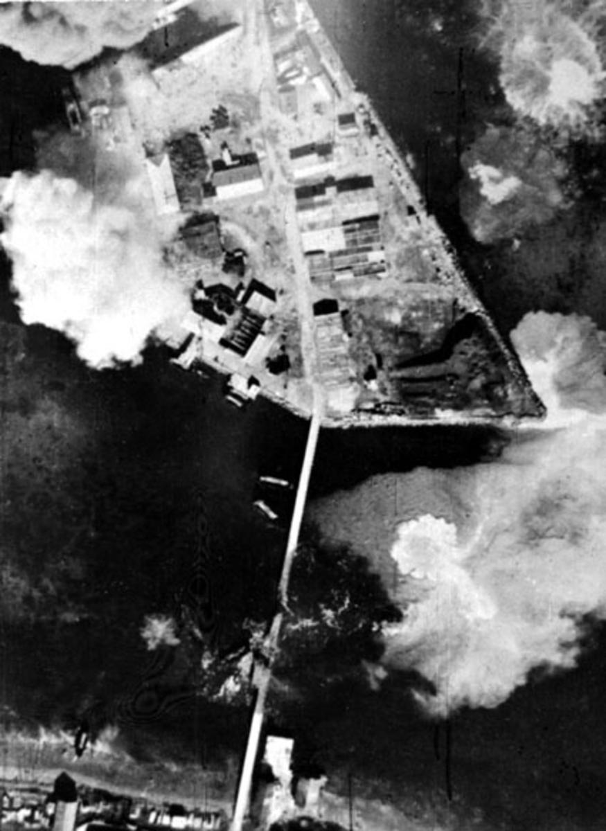 Luftfoto av tettsted ute ved kysten. Bebyggelse, havneanlegg. Røyk stiger opp etter bombeangrep.