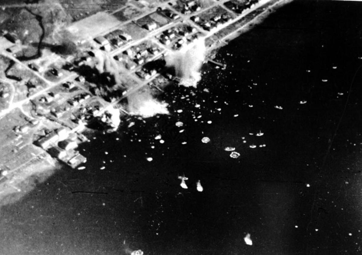 Luftfoto av tettsted ute ved kysten. Flere mindre fartøy, fiskebåter ligger på havna. Noe røyk stiger opp etter bombeangrep.