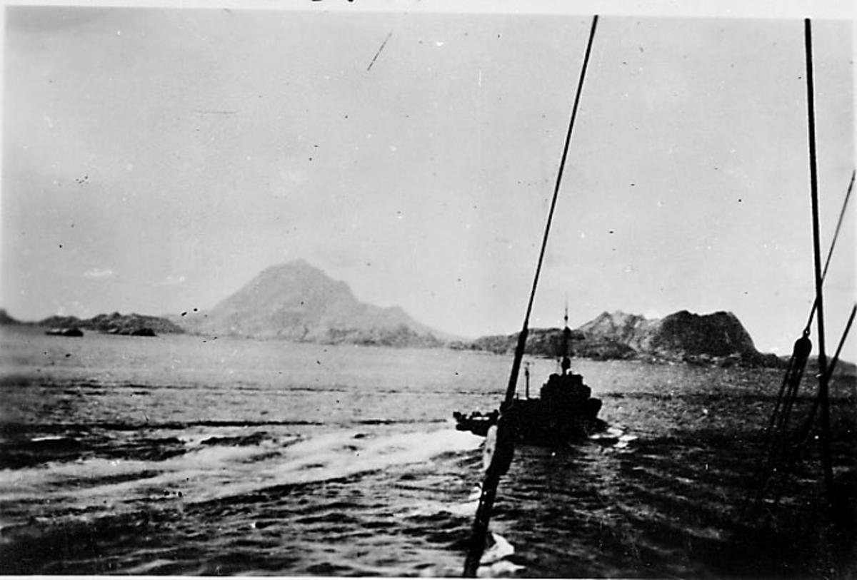 Fartøy i fart, land i bakgrunnen. Foto tatt fra annet fartøy. Narvik under 2. verdenskrig.
