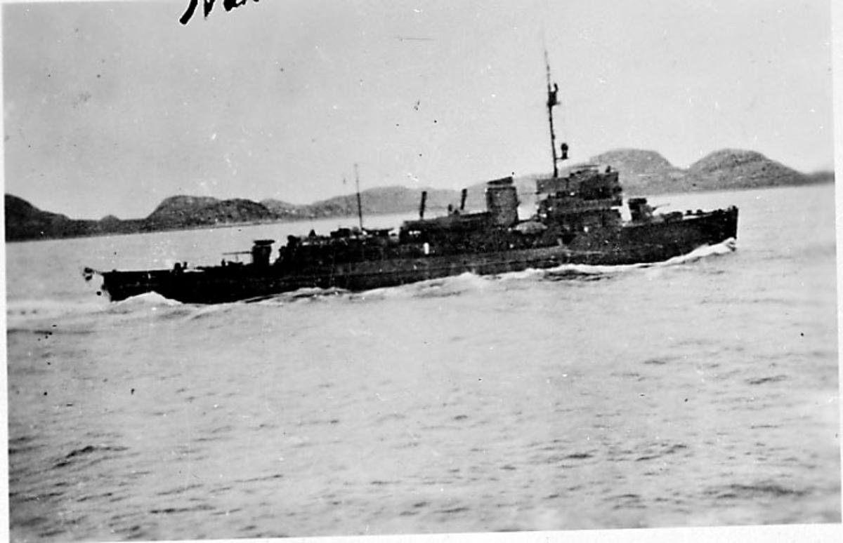 Marinefartøy i sakte fart, land i bakgrunnen. Narvik under 2. verdenskrig.