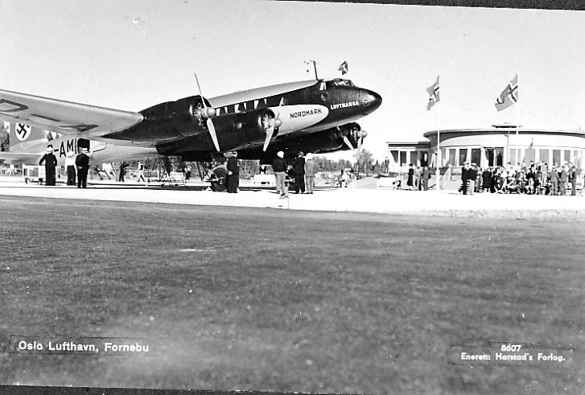 """Lufthavn, 1 fly på bakken Focke-Wulf Fw200 Condor D-AMHC """"Nordmark""""  fra lufthansa. Hakekors på haleparti.  Flere personer. Rund bygning med heiste flagg, bak."""