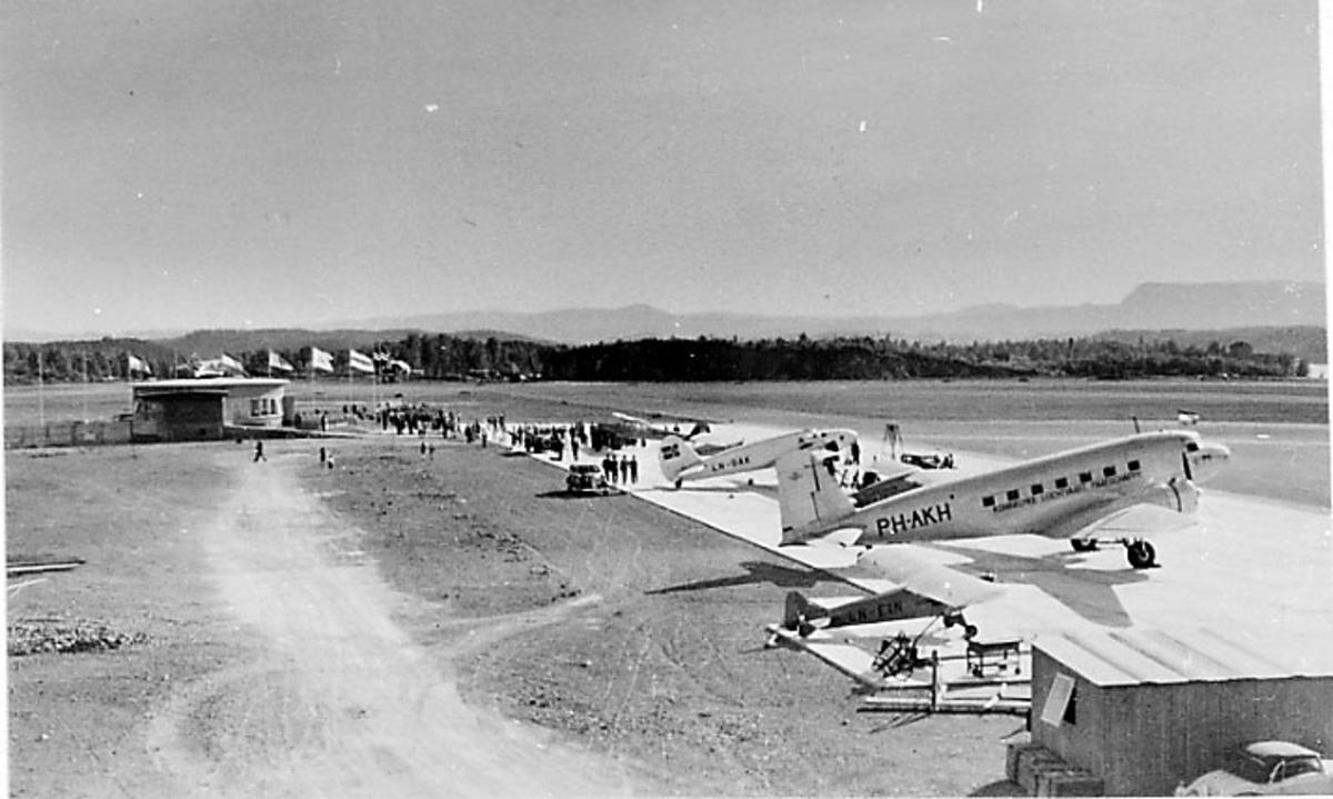 Lufthavn. Flere fly parkert på rekke. Flyplassbygning bak med flagg.