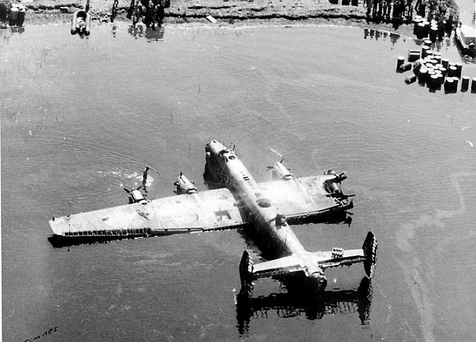 """1 fly ligger skadet på bakken delvis dekket av vann, Handley Page  Halifax """"S for Sugar"""", W.1048, fra RAF. Flere personer inne på land."""
