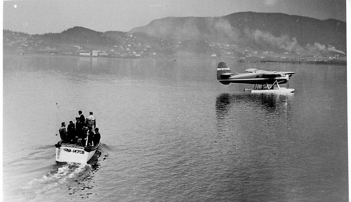 1 fly ligger rolig på havoverflata, DHC-3 Otter fra Widerøe. 1 åpen båt med personer ombord på vei til flyet - tilbringerbåt.