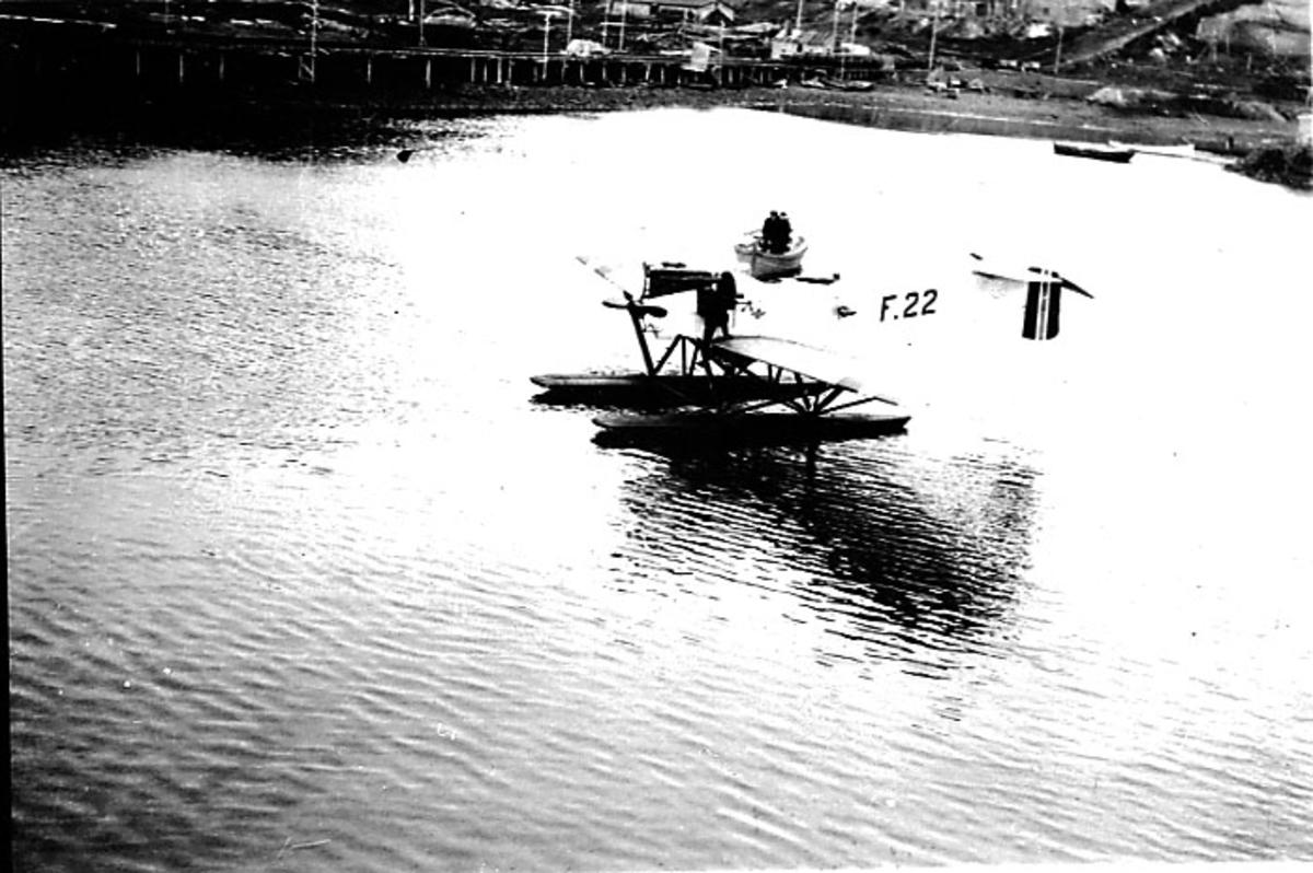 1 fly, Hansa-Brandenburger no F 22, ligger stille på havoverflata i havneområde. 1 person ved flymotooren