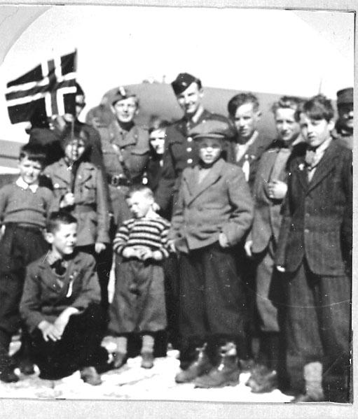 Lufthavn, gruppebilde, barn og voksne foran 1 fly. Holder det norske flagg. Tatt utendørs.