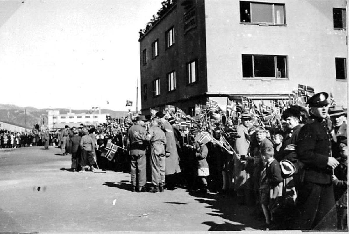 By, store folkemengder i gatene med norske flagg. Grand Hotell bak.