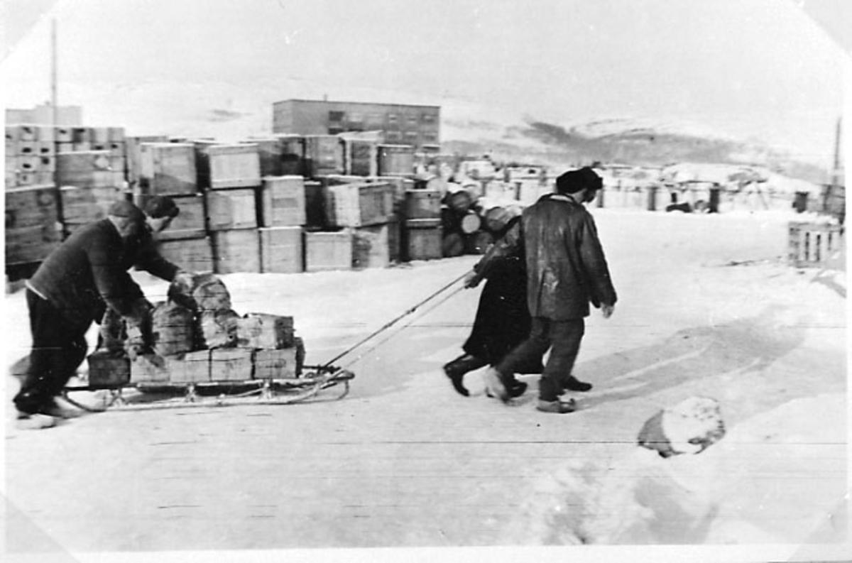 Anleggsområde - industriområde. Stabler med kasser - paller. 3 personer drar en kjelke bortover lastet med utstyr. Tatt utendørs. Snø på bakken.
