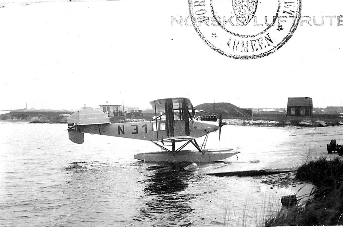 1 fly i vannkanten, LFG Strehla V13, N.31 LN-ABE, fra Norsk Luftruter A/S. Flere personer og kjøretøy i bakgrunnen.
