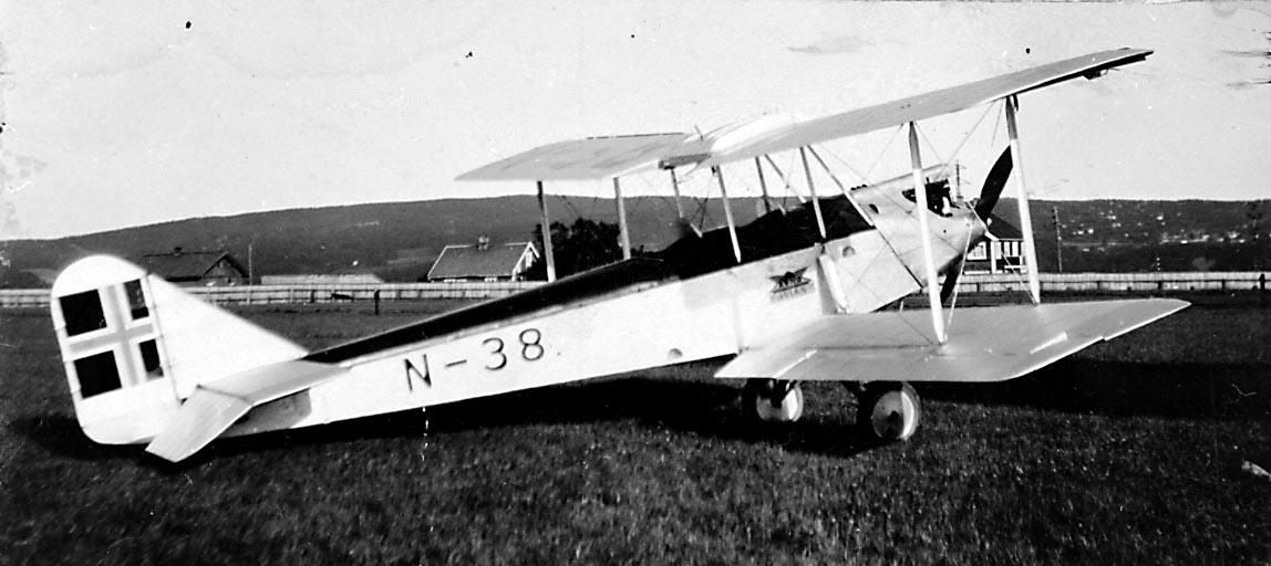 1 fly på bakken, Avro 594 Avian IV, N.38 LN-ABF fra A/S Norsk Lufttransport.  Bygninger i bakgrunnen.