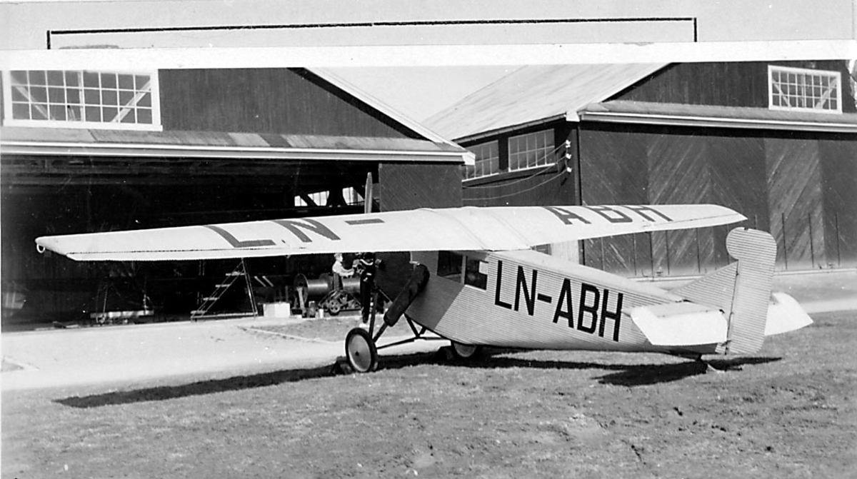 1 fly på bakken foran flere hangarbygninger, Junkers K-16 bi, LN-ABH fra Gidsken Jakobsen Narvik.