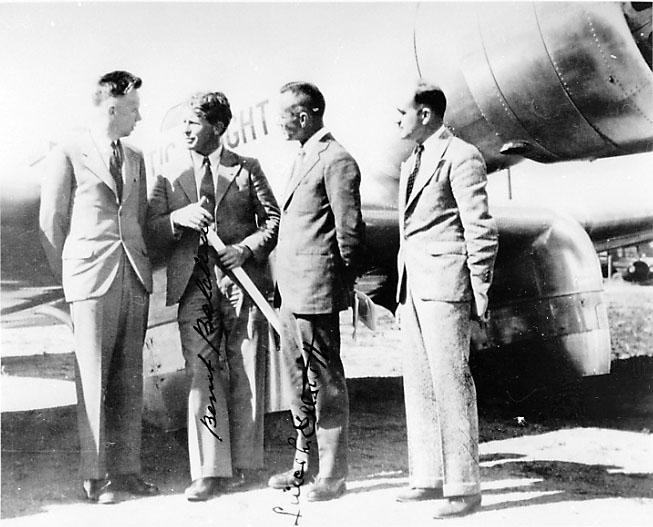 Gruppebilde. 4 personer, menn ved et fly.