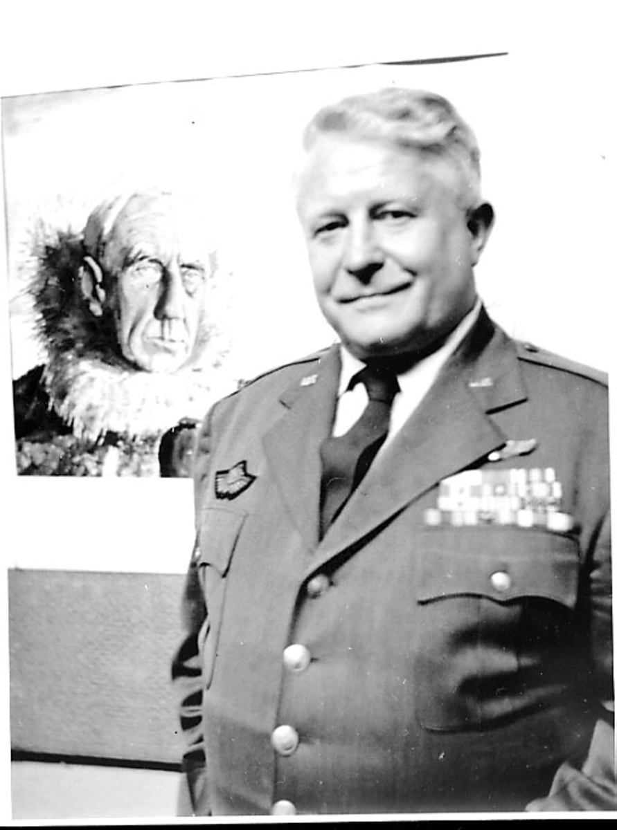 Portrett av person, mann i militæruniform foran et foto. Tatt innendøras av Roald Amundsen.