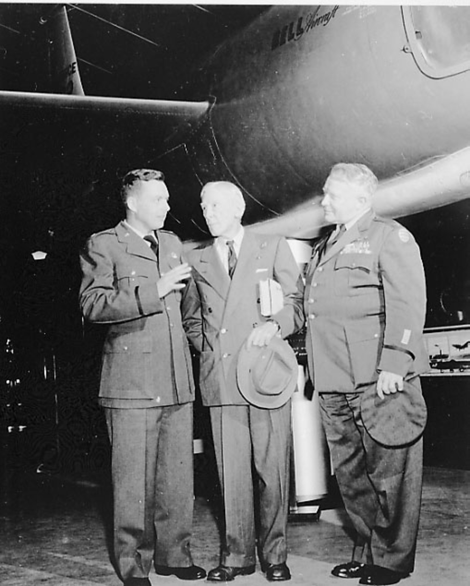 Gruppebilde. 3 personer, menn i militæruniform ved et fly.