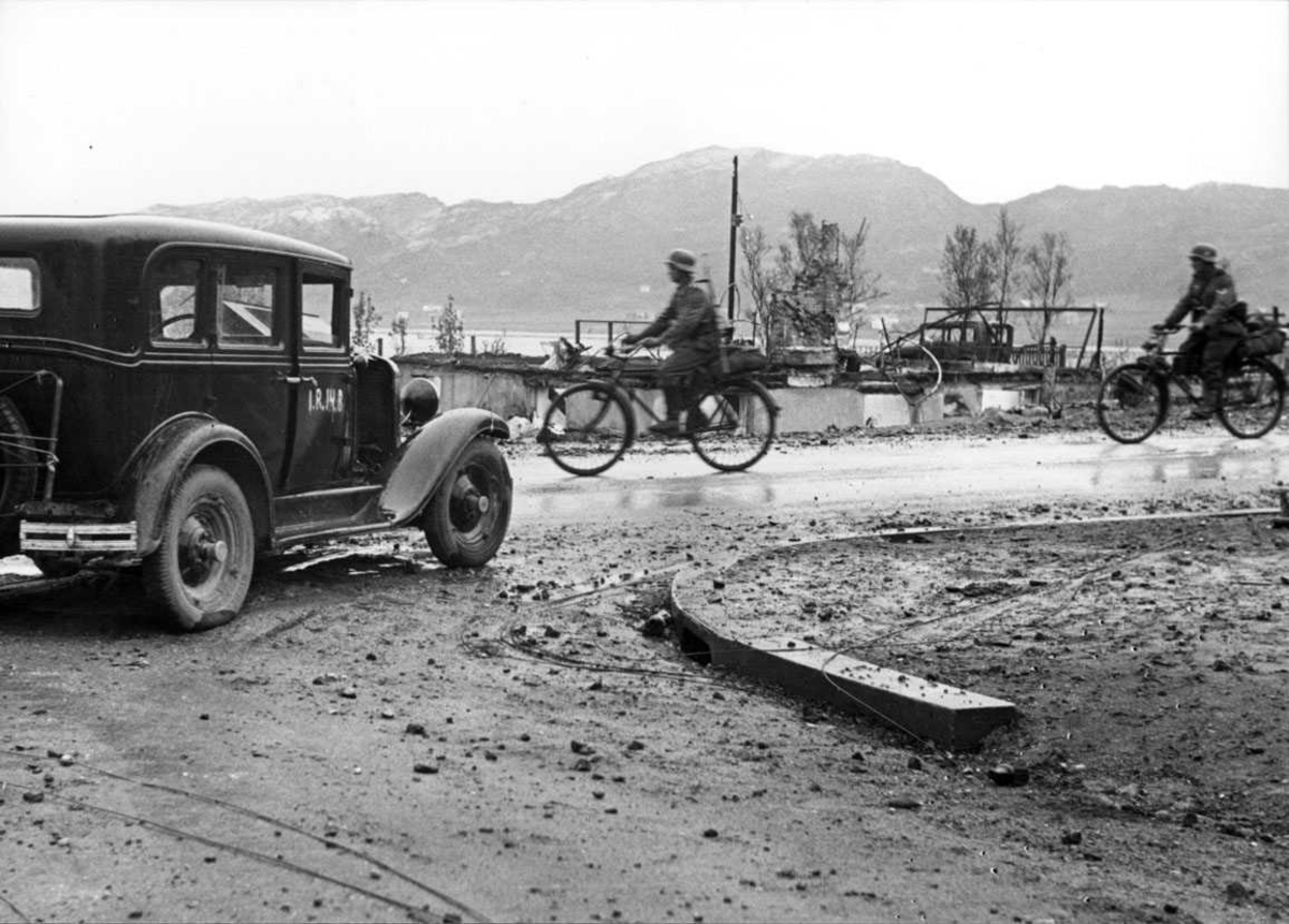By - tettsted. Vei med noen personer, menn i militæruniform på sykkel. Personbil - kjøretøy i forgrunnen. Ruiner av flere bygninger. Tyske soldater på snippen.