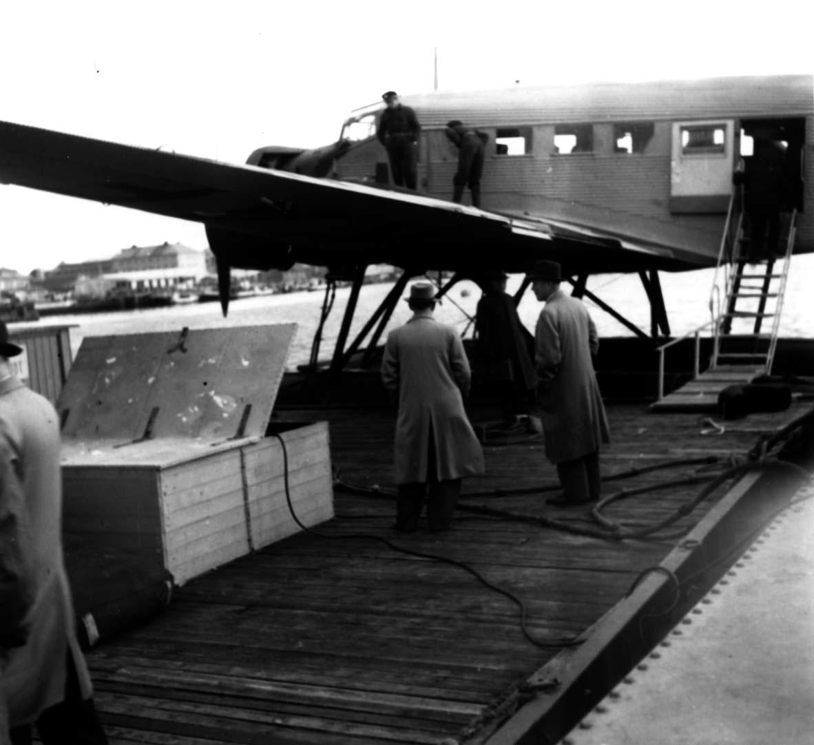 """Sjøflyhavn, Ett fly ligger ved kai, Junkers JU-52 3m mg LN-KAF """"Askeladden"""" fra DNL. Flere personer ved flyet."""