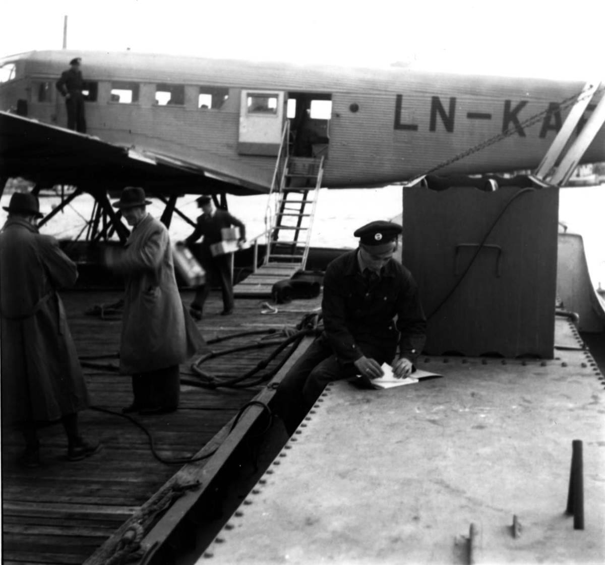 """Sjøflyhavn, Ett fly ligger ved kai, Junkers JU-52 3/mg LN-KAF """"Askeladden"""" fra DNL. Flere personer ved flyet."""