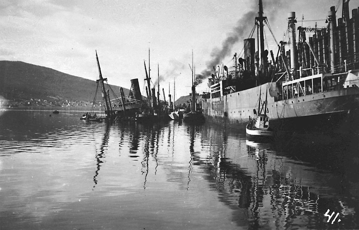 Havneområde. Flere skipsvrak. Ødelagte fartøy etter bombeangrep. Flere småbåter ved vrakene.