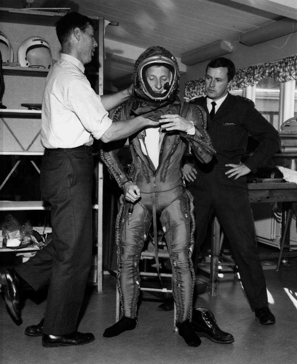 Gruppe.  Tre personer, to i uniform hjelper med påkledning av trykkdrakt.