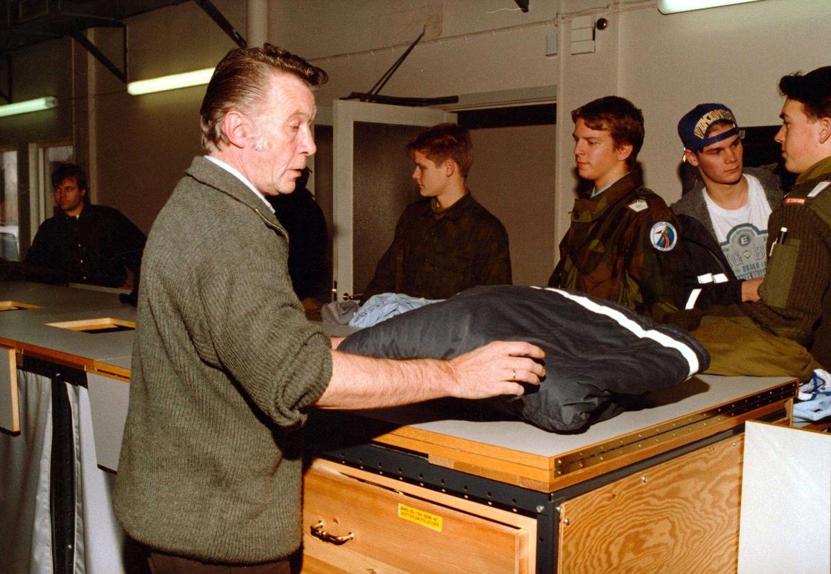 Lufthavn-flyplass.     Fem soldater bytter effekter og sengtøy, en fagarbeider ekspederer.