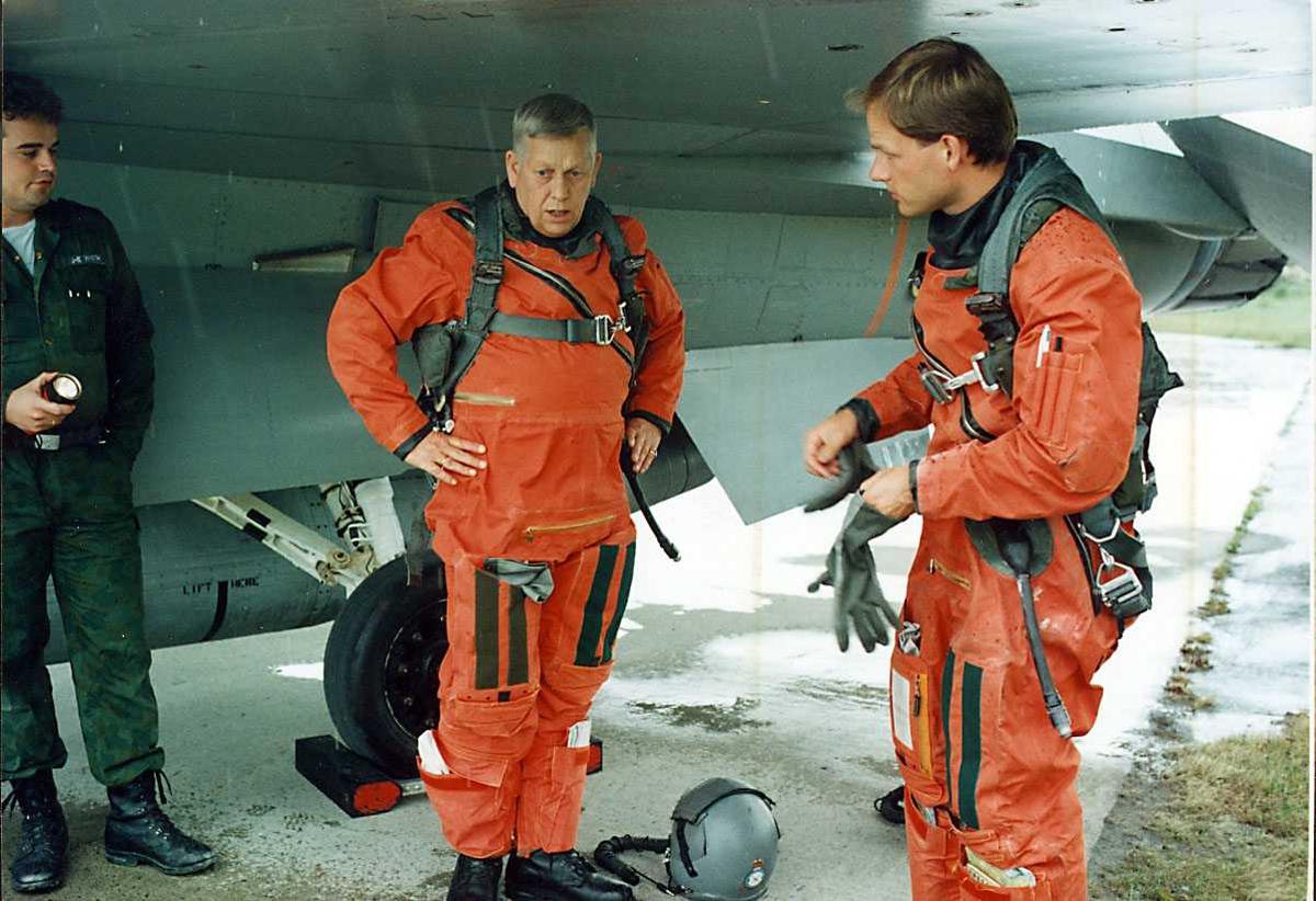 Gruppe. Tre personer ved en F-16.