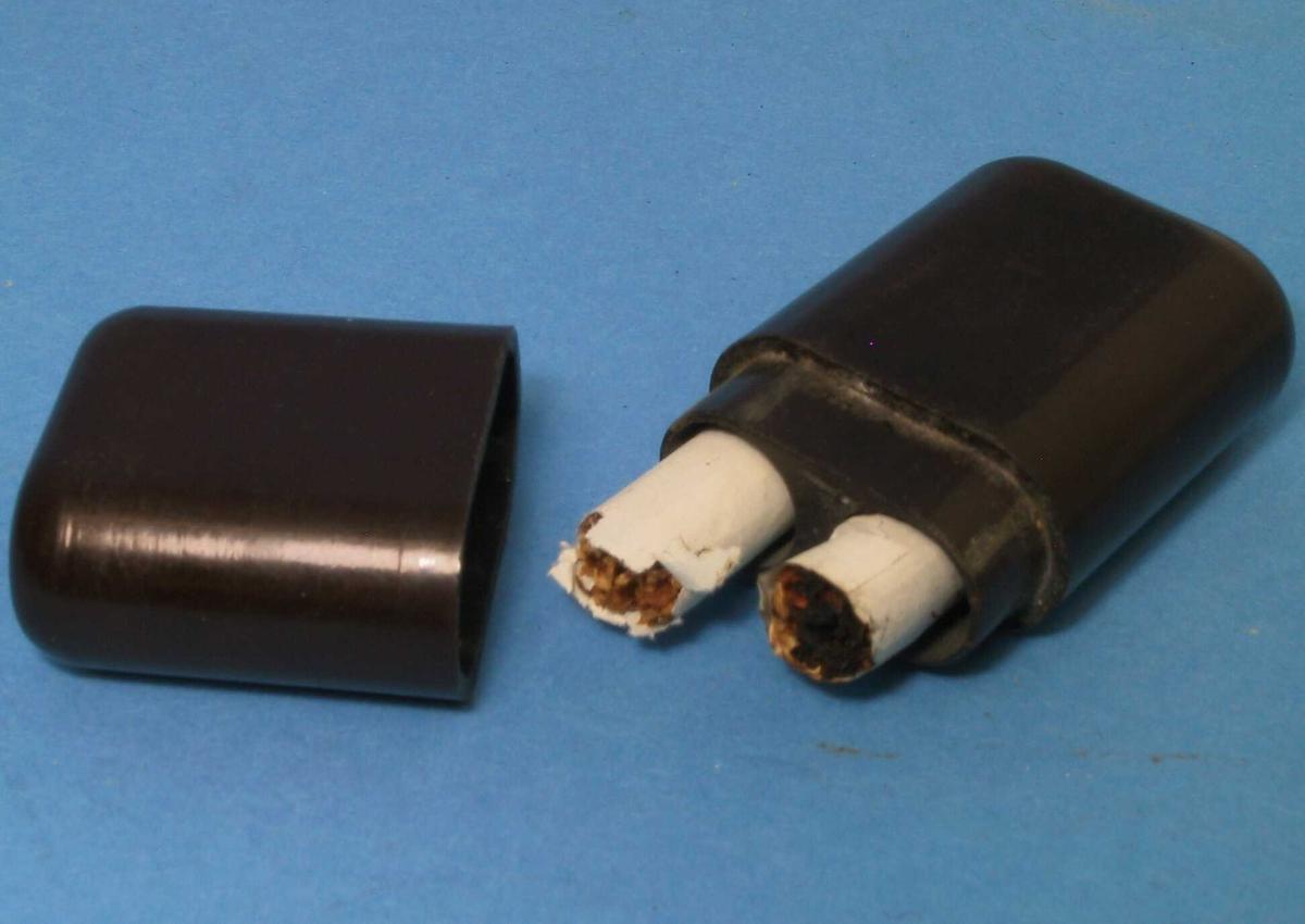 """Bakelittetui for to sigarettstumper.  Brun bakelitt.   Delt pm rektang. form med rundede sider,  innvendi plass til to """"sneiper""""."""