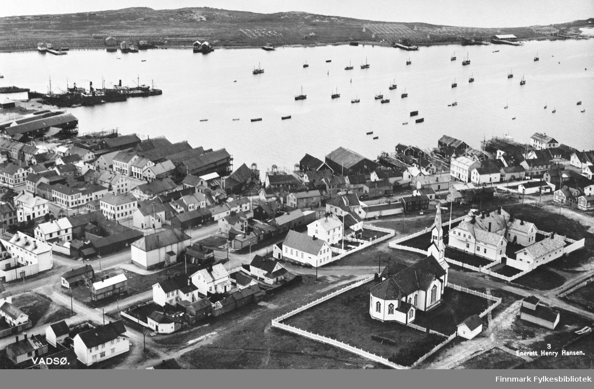 Et postkort fra Vadsø. Foran på bildet kirke og kirkegården. Bakerst fjorden og øyen. Bildet er tatt fra radiomastene.