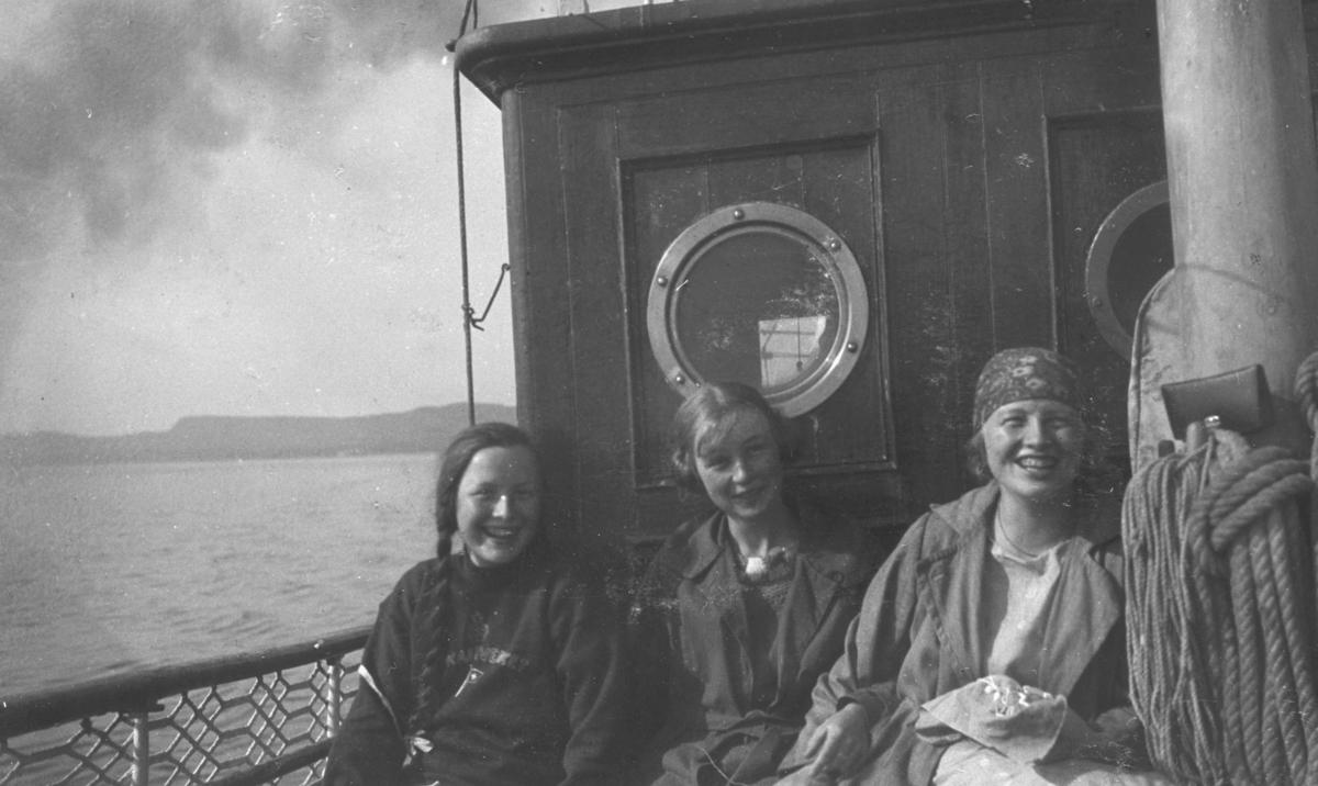 """Tre unge jenter, Biddi Hermansen, Eva og Ingrid Hermansen, fotografert om om bord på oppmålingsfartøy """"Wilhelm Huth"""". På albumet står det """"De glade Huth-dager i 1925"""". Bilder er ikke helt identisk med bildet nr. FBib.95053-011."""