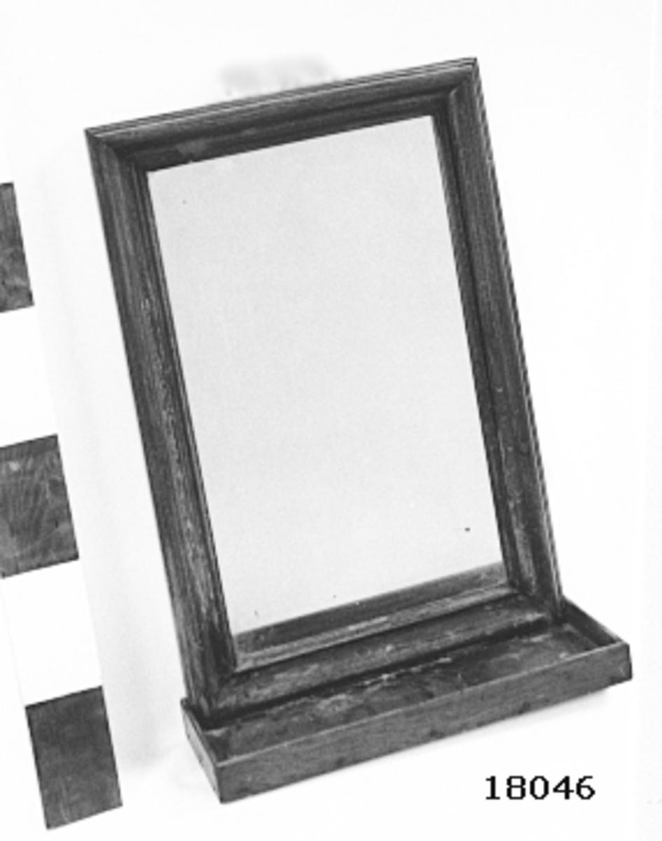 """Rektangulär spegel med profilerad ram och hylla av fernissad ek, ramens B = 50 mm. I nedrekanten fast hylla med rak hög kant. Baksida klädd med trä. Ögla på ramens överkant för upphängning. Märkt med stans: kronomärke typ kattfot samt """" THOR """". Text med blyerts: """" Thor Spegel i Uppbördsstyrmans Hytt mot aktra skott 1ste Styrman """"."""