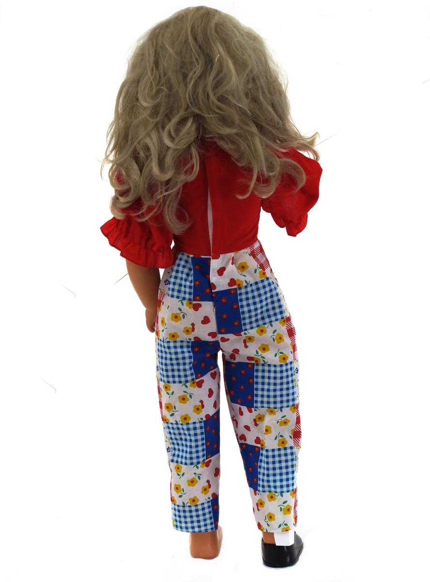"""Dukke av plast, Langt hår.  Bevegelige øyelokk. Dukken har bøyelige ledd i skulder og hofter.  med kjeledress i rødt, blått og hvitt. Sorte sko. Borrelås i ryggen på kjeledressen. """"Made in China"""" støpt inn i ryggen. Tilstand: God. En sko manglet ved innkomst."""