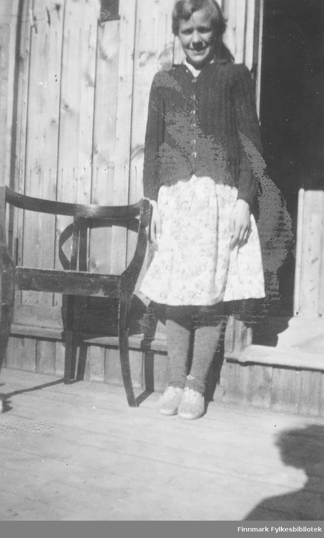 Åse Berg Aronsen fotografert utenfor brakke 19 i Vadsø ca. 1950-1951. Åse er kusine til Ragnhild Ebeltoft