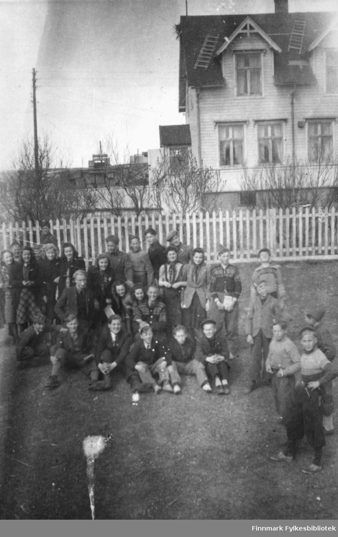 Middelskoleelever i Vadsø 1946-1947. Bildet kan være tatt ved Prestelva. Det ser ut til å være en bro på veien som går på oversiden av huset