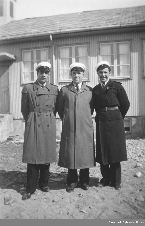 Medlemmer av Vadsø mannssangforening, med sangerluer. Fra venstre Erling og Halfdan Kvam, Oskar Store. Bildet kan være tatt omkring 1960. I bakgrunnen noe som ser ut til å være en gjenreisningskirke, men vi vet ikke hvor bildet er tatt