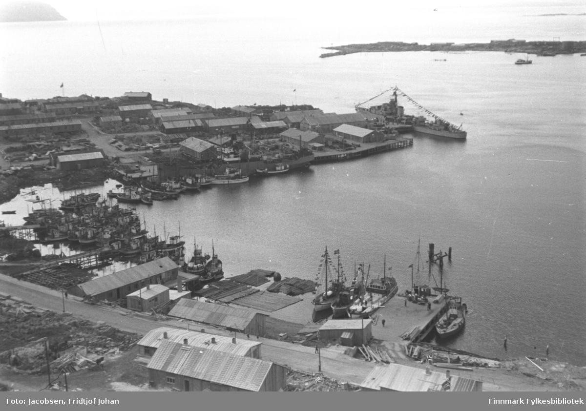 Sentrum øst, midtbyen sett fra fjellet Salen. KNM Stord ved kai. Kongen kom med denne 10. juli 1946. Båten ligger ved Gabrielsen-kaia. Mange båter ligger fortøyd i havna og noen ligger ved kaiene. Flere av dem har flagg og vimpler. Restene av båten som stikker opp av sjøen nede til venstre på bildet er FFR-båten Brynilen som ble senket ved Dampskipskaia under krigen. Mange brakker er satt opp langs Strandgata og på Hammerfest-neset, men endel ruiner ses enda. Det norske flagget henger på flaggstenger utenfor enkelte bygninger. En del el-stolper står langs gatene over hele området. På andre siden av havna/innseilingen til byen ses Fuglenesodden og oppe til venstre på bildet er øya Håja.