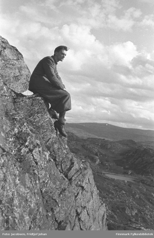 Fridtjof Jacobsen sitter på en fjellkant. Han er iført ganske mørke klær og sko. Terrenget rundt er kupert og en lite fjellvann ses nede til høyre på bildet.