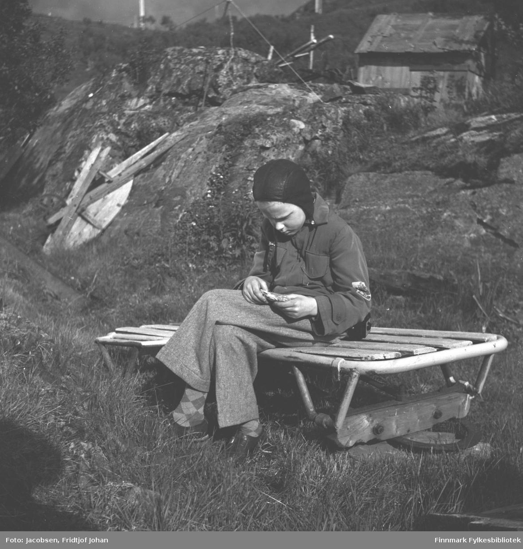 Arne Jacobsen på besøk hos sine besteforeldre, Arne og Sigrid Nakken. Han sitter på en liten, lav benk iført en lys slengbukse, litt mørkere jakke og sort lue. En stor stein står på tomta like bak han og en liten hytte/skur ses oppe til høyre på bildet. Noe gress ligger i terrenget der Arne sitter og noen løvtrær ses i området. Rester av en kabeltrommel ligger mot steinen til venstre på bildet.