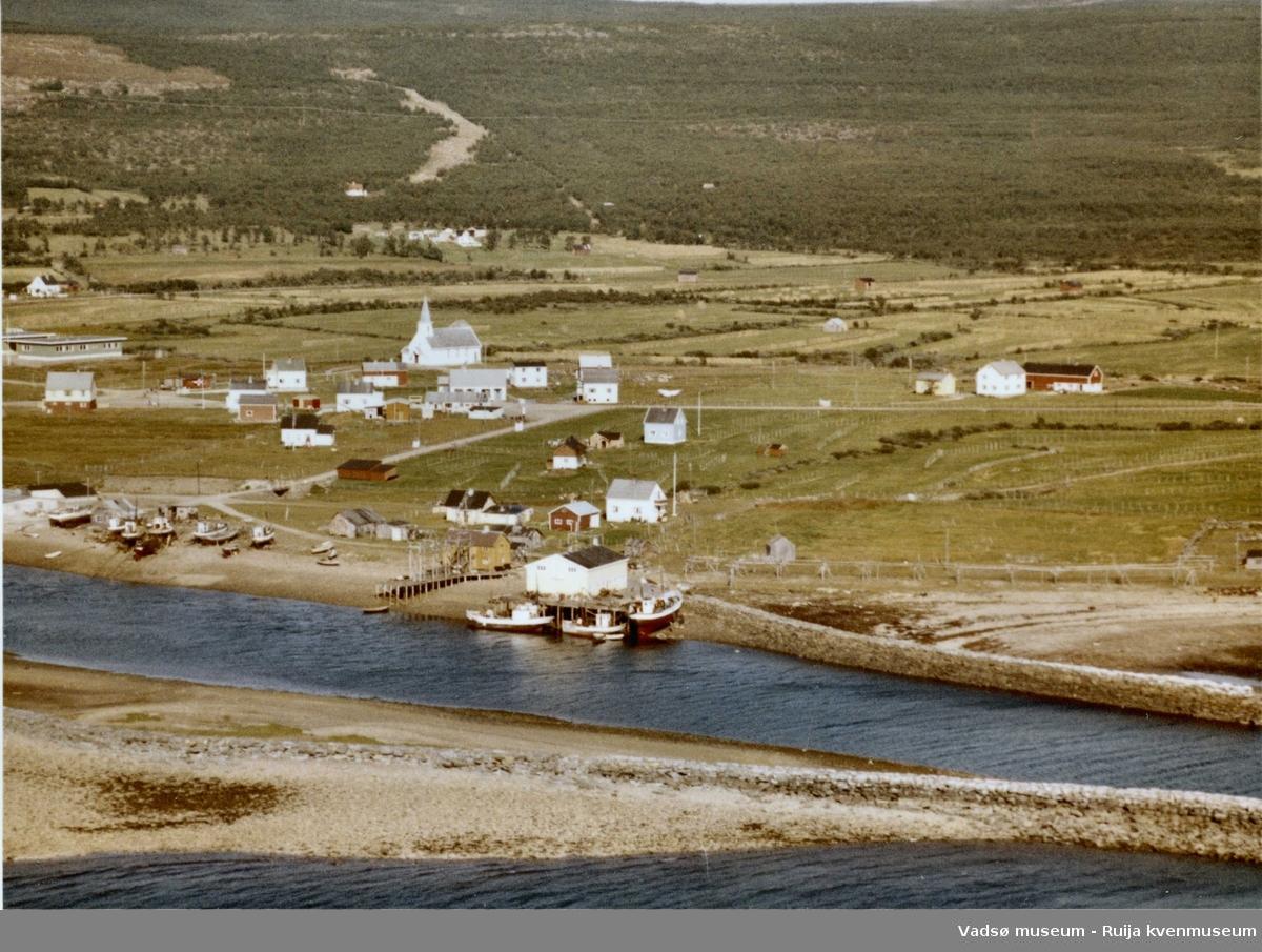 Flyfoto av Vestre Jakobselv, Vadsø kommune, 1963. Kirka midt i bildet. Litt av skolen helt til venstre i bildet.