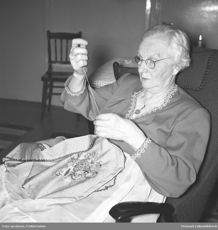 Olga Jacobsen, Arne Jacobsens farmor, sitter i en lenestol og broderer. Hun har en forholdsvis lys bluse, med mønster i halsen og rundt håndleddene, på seg. En pinnestol står ved siden av et bord bak henne. Et stearinlys brenner oppe til høyre på bildet.