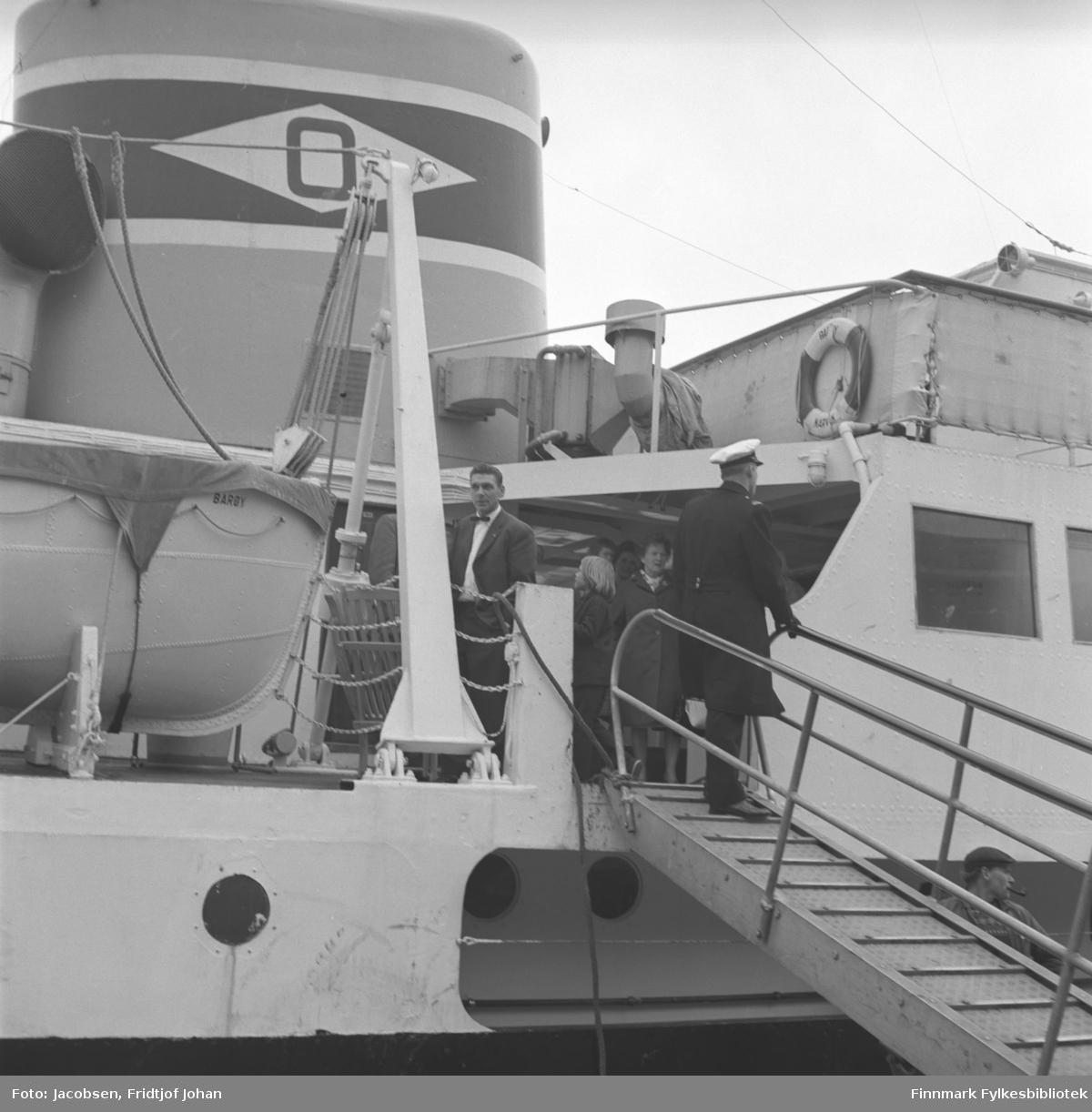 """Dette er hurtigruteskipet M/S Barøy, det står Barøy på livbåtsiden. Øverst på landgangen står en av offiserene iført uniform. En mann iført dress, hvit skjorte og sløyfe står på dekket like innenfor landgangen. Litt lengre inn på dekket står flere mennesker. Skorsteinen står øverst til venstre på bildet og har en O, for Ofoten Dampskipsselskap, påmalt og en livbøye henger på rekka oppe til høyre. Det står i skipshistorien at MS Barøy ble solgt til Fredrikstad i 1964. Dette må være """"avskjedsturen"""" fra hurtigruten."""