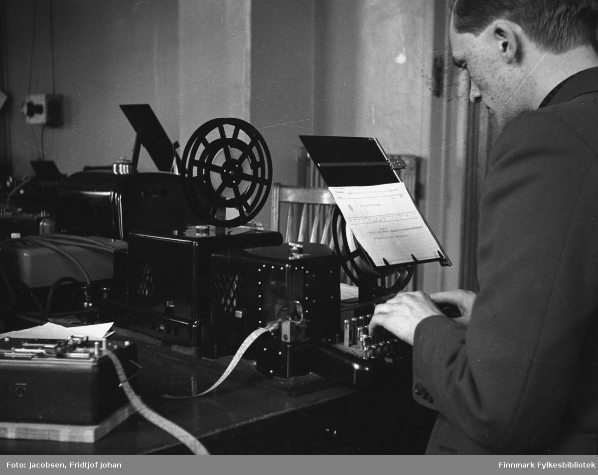 Telegrafverket (som det het til 1969) i Hammerfest. Telegramutskriving på start-stopp. Mannen på bildet er sannsynligvis Knut Ekrem. Han har en mørk jakke på seg og sitter med fingrene på telegrafiapparatet. En telegram ligger på konseptstativet og annet utstyr står på bordet foran.