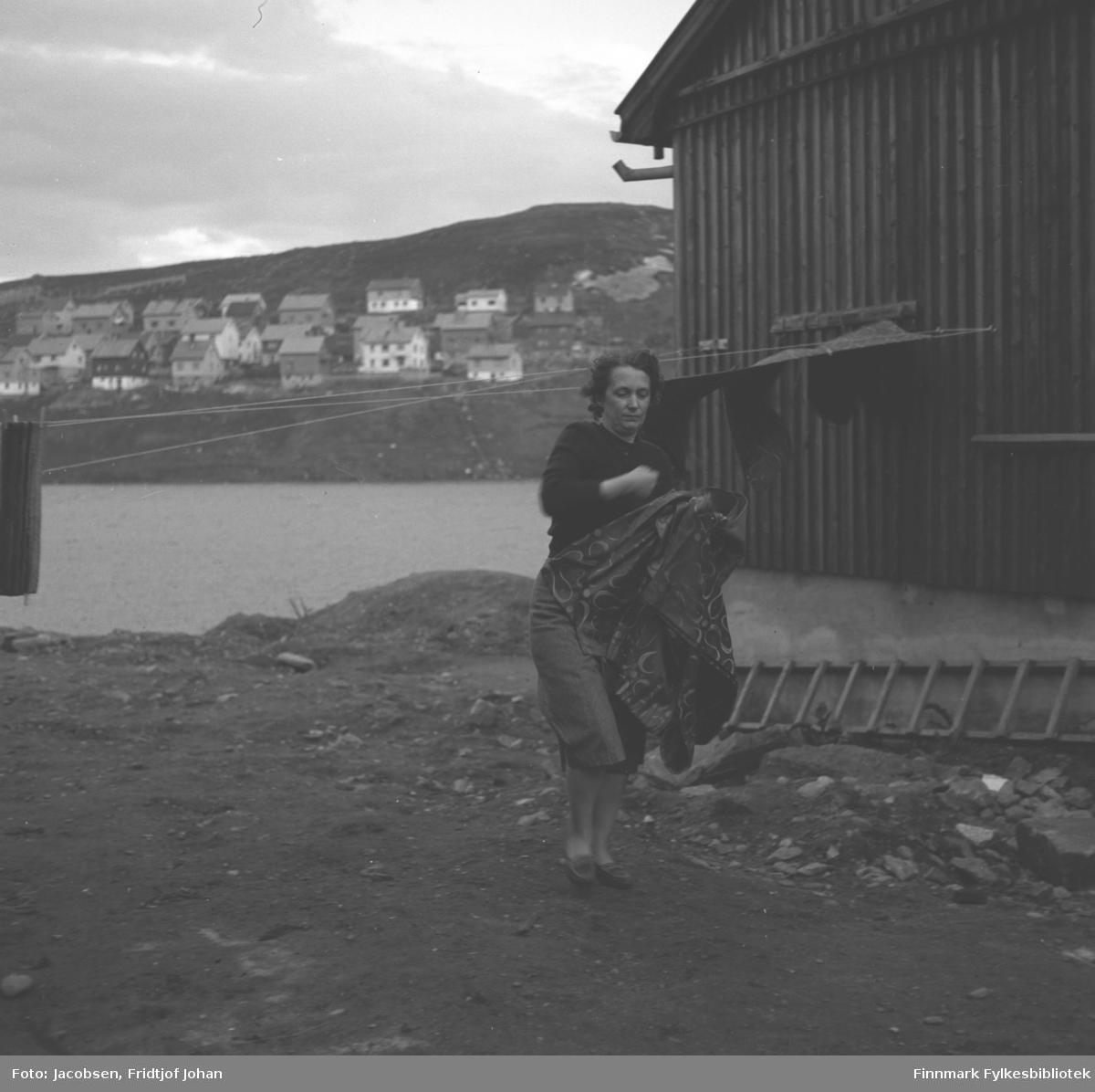 Aase Jacobsen tar inn klesvasken. Hun har en mørk genser og et litt lysere skjørt på seg. Huset har stående, mørkt panel og en slige ligger langs grunnmuren. Vannet litt bak henne er Storvannet og bebyggelsen i Idrettsveien og Skiveien ses i bakgrunnen. Bildet er tatt i Storvannsveien der hun og familien bodde